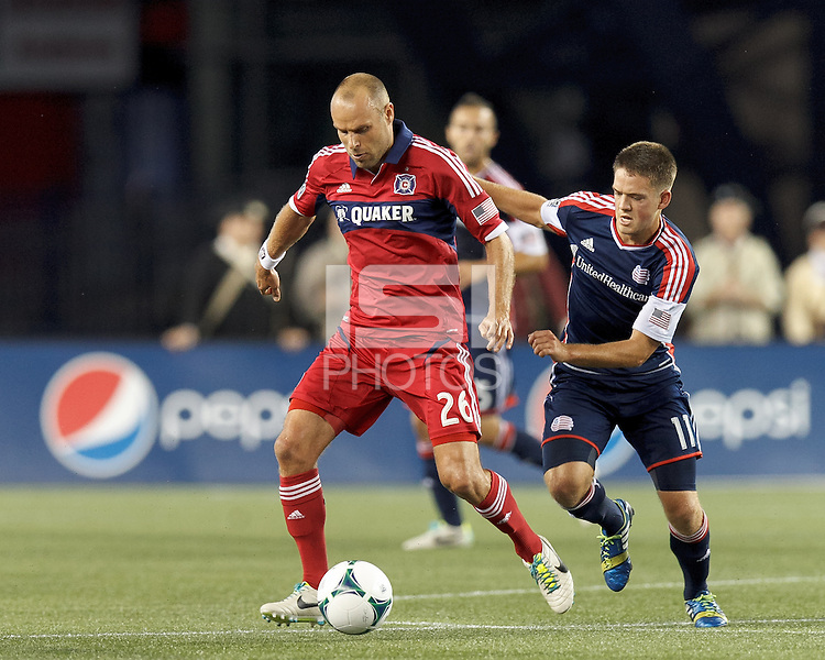 Chicago Fire midfielder Joel Lindpere (26) dribbles at midfield as New England Revolution midfielder Kelyn Rowe (11) closes. In a Major League Soccer (MLS) match, the New England Revolution (blue) defeated Chicago Fire (red), 2-0, at Gillette Stadium on August 17, 2013.