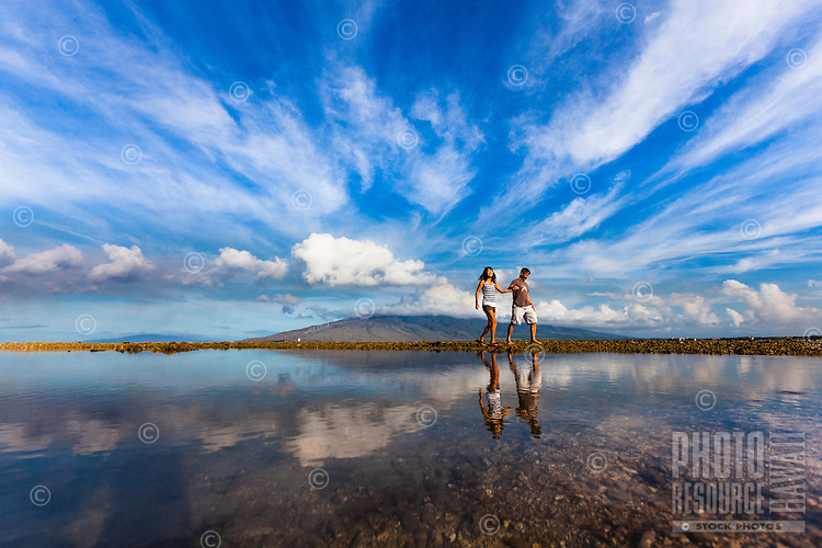 Happy couple walking around Koieie Fishpond in Kihei, Maui, with Lanai in the background.