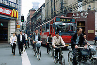 China. Shanghai. Downtown. City center. Workers ride bikes on their way to work . A public bus passes on the road near a Mac Donald restaurant, while a couple crosses the street on a green light. © 2002 Didier Ruef