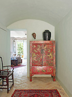 An antique red and gold hand-painted Chinese cabinet next to a doorway into the living area