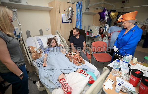 25 May 2017 - Queen Elizabeth II speaks to Evie Mills, 14, from Harrogate, her mother, Karen and dad, Craig, during a visit to the Royal Manchester Children's Hospital to meet victims of the terror attack in the city earlier this week and to thank members of staff who treated them. Photo Credit: ALPR/AdMedia
