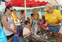 NWA Democrat-Gazette/FLIP PUTTHOFF<br /> 10 YEARS FOR SECCHI DAY<br /> Tina Gaither (from left), her son, Isaac, 5, and daughter Sophie, 11, learn about the Beaver Lake watershed from Steve Sampers (right) on Saturday August 15 2015 during the 10th annual Secchi Day. Teams of volunteers fanned out on all areas of the lake to measure the water's transparency with a Secchi Disk. Data is compiled at Prairie Creek park where volunteers eat a complimentary lunch, see educational exhibits and win door prizes. Data from 10 years of Secchi Day events helps water officials spot any trends or changes in the clarity of the reservoir, said Bob Morgan with the Beaver Water District, which provides drinking water to most of the region. Beaver Lake is the water source for Northwest Arkansas and beyond.