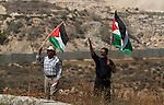 Palestinian protesters  hold their national flags during a protest against Israel's separation barrier and in solidarity with Palestinian prisoners being held in Israeli jails, in the West Bank village of Bilin near Ramallah August 30, 2013. Photo by Issam Rimawi