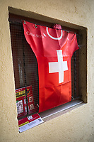 "Switzerland. Canton Ticino. Vezia. A plastic shirt of the Swiss Football team and a prevention poster again Coronavirusalso called Covid-19) are fixed on a window inside the courtyard of a private house. The Swiss Football Association (SFV) has for sponsor the multi-national investment bank and financial services company Credit Suisse. The Coronavirus poster explains how to prevent from getting the disease. The measures are: Keep your distance, wash your hands thoroughly, avoid shaking hands, cough and sneeze into a tissue or the crook of your arm, stay at home if you have fever, always call ahead before going to the doctor's or the emergency department. Due to the spread of the coronavirus, the Federal Council has categorised the situation in the country as ""extraordinary"". It has issued a recommendation to all citizens to stay at home, especially the sick and the elderly. The Federal Council (German: Bundesrat, French: Conseil fédéral, Italian: Consiglio federale, Romansh: Cussegl federal) is the seven-member executive council that constitutes the federal government of the Swiss Confederation. From March 16 the government ramped up its response to the widening pandemic, ordering the closure of bars, restaurants, sports facilities and cultural spaces. Only businesses providing essential goods to the population – such as grocery stores, bakeries and pharmacies – are to remain open. Vezia is a municipality in the district of Lugano. <br /> The flag of Switzerland displays a white cross in the centre of a square red field. The white cross is known as the Swiss cross. Credit Suisse Group AG is a global wealth manager, investment bank and financial services company founded and based in Switzerland. 27.03.2020 © 2020 Didier Ruef"
