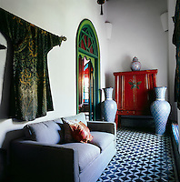 The seating area has a blue and white patterned floor and green painted arched doorway. A grey sofa stands against one wall and two tall urns are placed in front of a wooden cabinet.