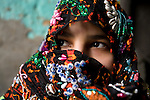 A young, local Siwan woman wears traditional hand-made clothing inside her home in Siwa Town of the Siwa Oasis, Egypt.