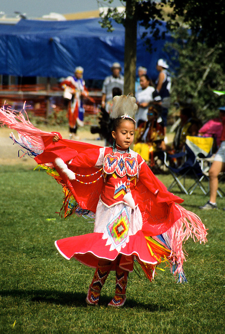 Young Chippewa-Cree girl dressed in colorful dress and long fringed shawl dances the fancy shawl dance during the Chippewa-Cree pow wow on the Rocky Boy Indian Reservation, Montana