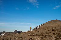 Female hiker hiking over rocky slopes near summit of Hestræva, Flakstadøy, Lofoten Islands, Norway