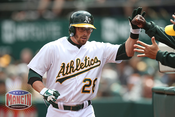 OAKLAND, CA - APRIL 2:  Eric Sogard #28 of the Oakland Athletics celebrates with his teammates after scoring a run against the Cleveland Indians during the game at O.co Coliseum on Wednesday, April 2, 2014 in Oakland, California. Photo by Brad Mangin