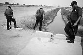 Culiacan, Mexico<br /> June 13, 2007<br /> <br /> The police search the site of a drug related execution, adding to the more then 300 this year in Cuilacan. Francisco de Jesús Ibarra, 33 was found lying in a canal on the outskirts of San Pedro. He had been beaten and shot in the head.