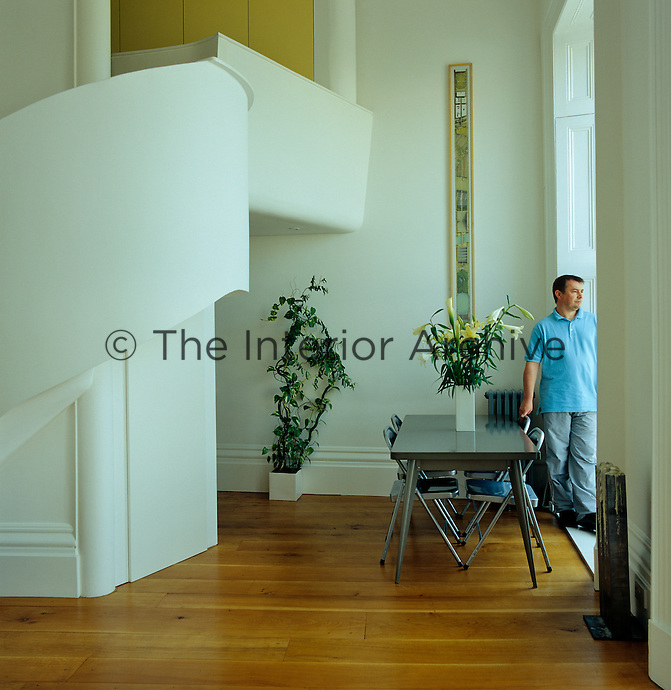 Designer Andrew Birds surveys the street from the tall window of his first-floor apartment