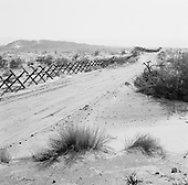Calexico, California<br /> USA<br /> August 20, 2007<br /> <br /> In 2007 the National Guard has placed miles of vehicles barriers along a western stretch of open desert that marks the border between the US and Mexico. The barrier now blocks what was once an open road for smugglers who simply drove vehicles loaded with drugs into the US.