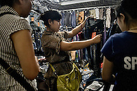 People shop for clothing at a wholesale market in the Fuzi Miao area of Nanjing, Jiangsu, China.  The market acts as a distributor of consumer goods to shops and smaller markets throughout the city.