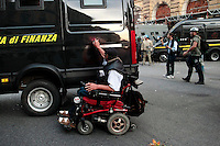 Scontri tra manifestanti e Guardia di Finanza davanti al Ministero dell'Economia. Un uomo disabile scrive con una bomboletta su un blindato della Finanza<br /> Fighting between the police and protesters in front of the Ministry of the Economy. A disabled protester writes on a tank of the police<br /> Roma 19-10-2013 Manifestazione Assedio all'austerity.<br /> Demostration - Siege the austerity.<br /> Photo Samantha Zucchi Insidefoto