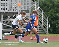 Boston Breakers defender Maddy Evans (18) dribbles down the wing as Seattle Reign FC midfielder Kristen Meier (21) defends. In a National Women's Soccer League (NWSL) match, Seattle Reign FC (white) defeated Boston Breakers (blue), 2-1, at Dilboy Stadium on June 26, 2013.