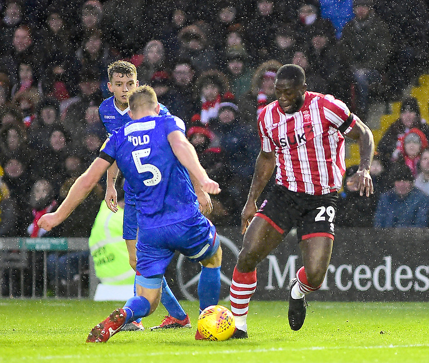 Lincoln City's John Akinde nutmegs Morecambe's Steven Old<br /> <br /> Photographer Andrew Vaughan/CameraSport<br /> <br /> The EFL Sky Bet League Two - Saturday 15th December 2018 - Lincoln City v Morecambe - Sincil Bank - Lincoln<br /> <br /> World Copyright © 2018 CameraSport. All rights reserved. 43 Linden Ave. Countesthorpe. Leicester. England. LE8 5PG - Tel: +44 (0) 116 277 4147 - admin@camerasport.com - www.camerasport.com