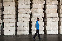A worker walks past raw cotton stacks in the Raw Material Godown of the Pratibha vertically integrated garment unit in Indore, Madhya Pradesh, India on 11 November 2014. Photo by Suzanne Lee for Fairtrade