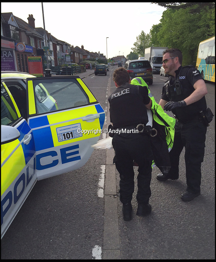BNPS.co.uk (01202 558833)<br /> Pic: AndyMartin/BNPS<br /> <br /> PC Mel Rooney and PC Dan Meeks put the swan in to the back of their police car.<br /> <br /> It's a swan-vesta...<br /> <br /> This is the hilarious moment two police officers captured a runaway swan - by throwing a hi-vis jacket over it.<br /> <br /> Bemused motorists reported seeing the stray water bird waddling along a pavement next to a busy road in Christchurch, Dorset, during rush hour.<br /> <br /> PC Mel Rooney and PC Dan Meeks used his bright yellow coat to throw over the bird in order to trap it.