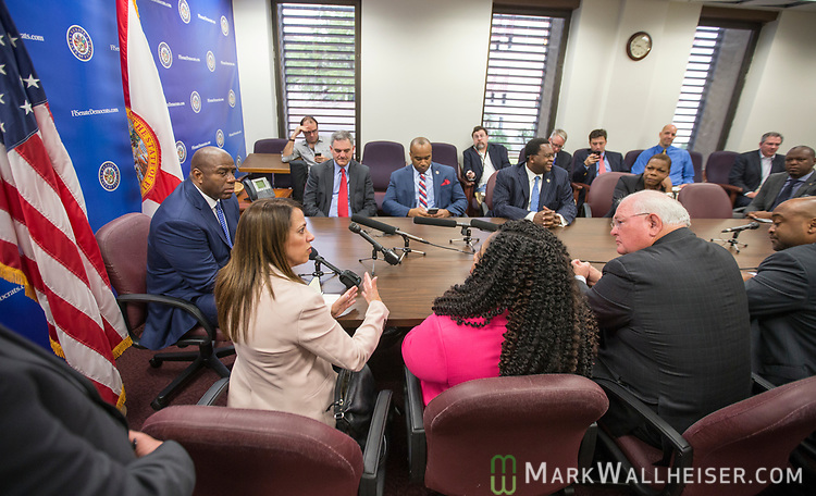 "Earvin ""Magic"" Johnson, retired professional basketball player and current president of operations for the Los Angeles Lakers of the NBA, left, listens as Lourdes Rivas, CEO of Simply Healthcare speaks during a meeting with the Florida Senate Democratic Caucus  about health care at the Florida Capitol in Tallahassee Florida March 13, 2017."