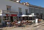 People sitting in sunshine outside street cafes in Praca da Republica, Tavira, Algarve, Portugal, Southern Europe