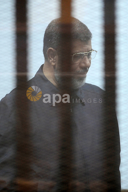 Former Egyptian president Mohamed Morsi sits in the defendants cage as he attends his trial at the police academy on the outskirts of the capital, on June 14, 2015. Cairo criminal court resumes Sunday the trial of deposed president Mohamed Morsi and 10 others on charges of espionage and leaking classified documents related to the national security and the army. Photo by Amr Sayed