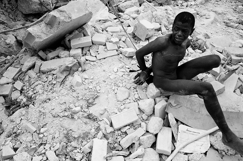 Port Au Prince, Haiti, Jan 25 2010.A young looter captured by the police. Everyday since the disaster, thousands of inpoverished inhabitants try to recover valuable goods in the ruins of downtown Port-au-Prince; sometimes it turns into downright looting of warehouse or shops; the police acts vigorously against the looters but it is sometimes difficult to draw the line between 'honnest' recovery and looting..