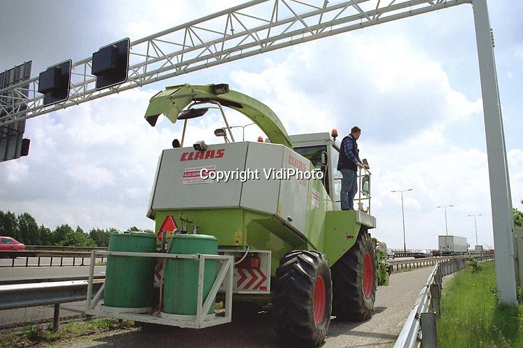 Foto: VidiPhoto..HEELSUM - Loon- en Grondverzetbedrijf E. Gerritsen uit Heelsum mag na 27 niet meer over het fietspad van de Heterense brug (A50). De loonwerker vreest daardoor een schadepost van miljoenen guldens. De meeste klanten bevinden zich namelijk aan de overkant van de Rijn. Rijkswaterstaat heeft het fietspad smaller gemaakt, waardoor het niet meer mogelijk is met .landbouwwerktuigen van meer dan 2.70 meter over het fietspad te rijden. In noodgevallen gebruikt Gerritsen de vluchtstrook langs de A50. Rijkswaterstaat vindt gebruik van het fietspad door landbouwverkeer te gevaarlijk. De Heelsumse loonwerker moet nu bij Arnhem de brug over of met .het Lexkesveer in Wageningen. In beide gevallen is dat een omweg van minstens anderhalf uur per keer. In het hoogseizoen maakte hij soms honderd maal per dag gebruik van het fietspad. Boeren in de Betuwe dreigen met acties als Rijkswaterstaat de zaak niet snel ongedaan maakt..