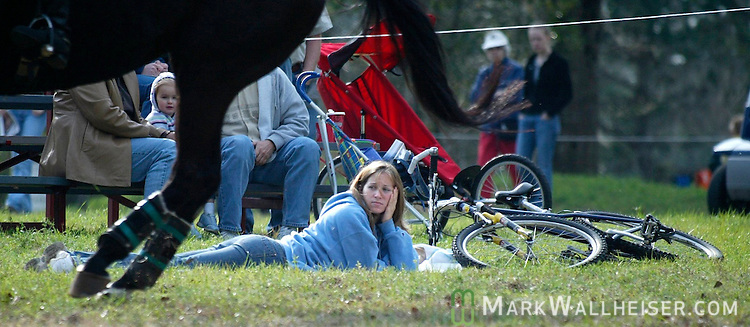 Sara Gonzalez-Rothi, of Gainesville, abandons her bike and takes a relaxed approach to watching the Red Hills Horse Trials in Tallahassee, Florida March 13, 2004. Gonzalez-Rothi is an ameture equestrian and this is her sixth Red Hills to attend. (Mark Wallheiser/TallahasseeStock.com)