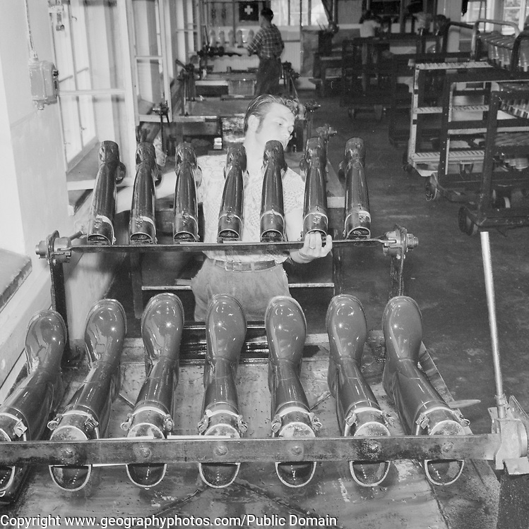 Male machine operator in factory making rubber boots footwear, Finland 1959