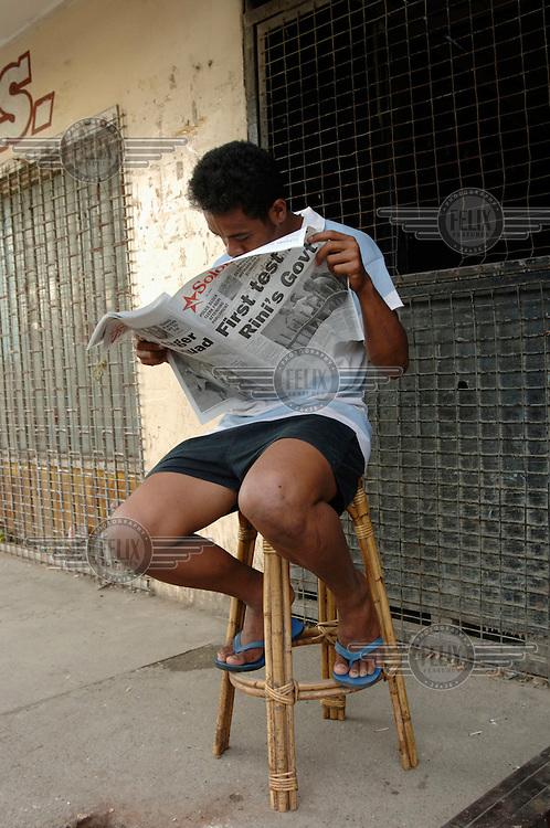 A man avidly reads the newspaper in the early morning. 'First Test for Rini's Government' headlines the Solomon Star. One hour later Snyder Rini resigned as Prime Minister. Rini had become PM just a week earlier, but his promotion had prompted mass protests because of corruption allegations.