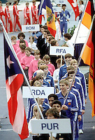 Several gymnastic teams march-in during opening ceremony at 1985 World Championships in women's artistic gymnastics at Montreal, Canada in mid-November, 1985.  Including front holding East German flag is Silvio Kroll. Photo by Tom Theobald.