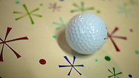 A golf ball rests on a sheet of wrapping paper.  (Photo by Brian Cleary/www.bcpix.com)