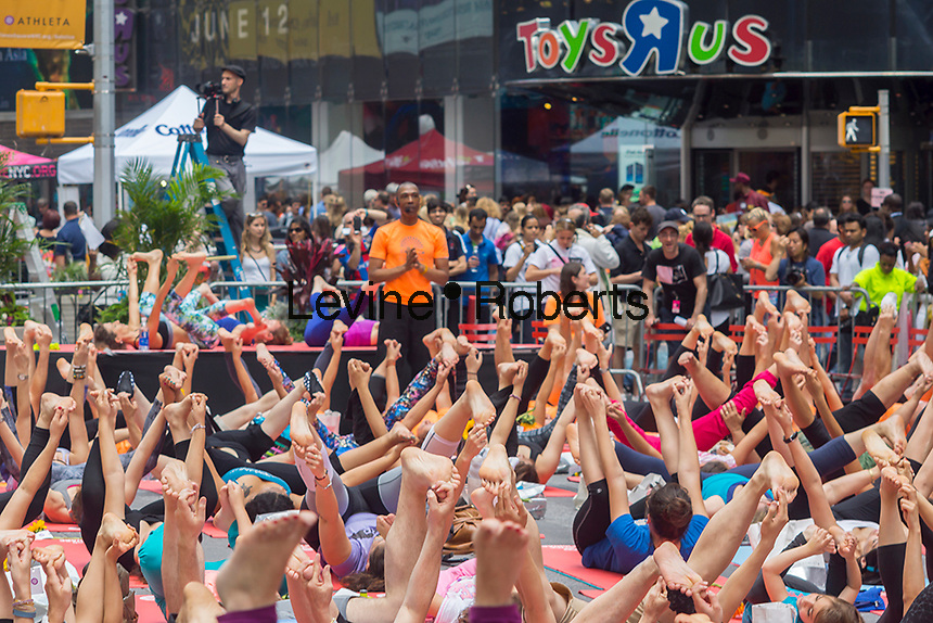 """Thousands of yoga practitioners pack Times Square in New York to practice yoga on the first day of summer, Sunday, June 21, 2015. The 13th annual Solstice in Times Square, """"Mind Over Madness"""",  this year takes place on the United Nations' International Day of Yoga. Times Square stretches the yogis' ability to block out the noise and the visual clutter that surround them in the Crossroads of the World. (© Richard B. Levine)"""