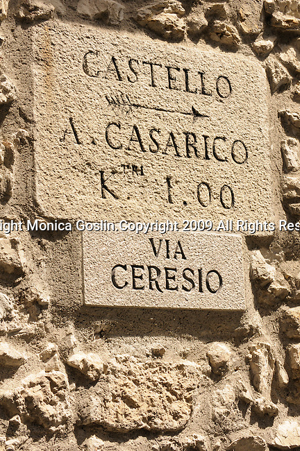A carved sign on a building pointing to the direction of a town from Castello, a town in the mountains on Lake Lugano, Italy.