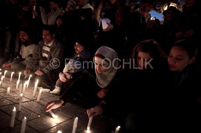 © Remi OCHLIK/IP3 -  Tunis Tunisia - People gather around candles in Tunis, Saturday, Jan. 22, 2011. Tunisians began three days of mourning Friday, lowering flags and broadcasting recitations of the Quran to mourn dozens who died in the protests that drove their autocratic leader from power.