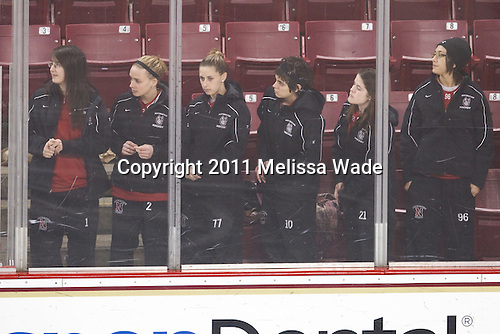 The Northeastern Huskies including Leah Sulyma (NU - 1), Dani Rylan (NU - 2), Lori Antflick (NU - 77), Autumn Prouty (NU - 10), Corinne Henning (NU - 21) and Danielle Kerr stand at the glass during the Hall of Fame introductions. - The Boston College Eagles defeated the Harvard University Crimson 3-1 to win the 2011 Beanpot championship on Tuesday, February 15, 2011, at Conte Forum in Chestnut Hill, Massachusetts.