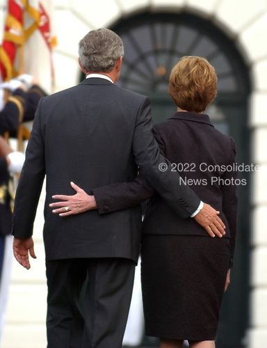 Washington, D.C. - September 11, 2004 --  United States President George W. Bush and first lady Laura Bush walk back to the Diplomatic Entrance of the White House in Washington, D.C. on September 11, 2004 after observing a moment of silence marking 3 years from the moment of the first terrorist attack on the World Trade Center in New York on September 11, 2001.<br /> Credit: Ron Sachs / CNP