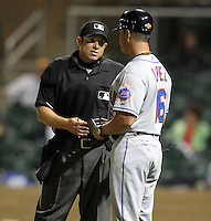 Home plate umpire Tripp Gibson explains a call to manager Pedro Lopez #16 during an Arizona Fall League game between the Salt River Rafters and Peoria Javelinas at HoHoKam Park on November 3, 2011 in Mesa, Arizona.  Salt River defeated Peoria 13-4.  (Mike Janes/Four Seam Images)
