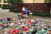 A woman drives her grandchild past a garbage heap at a housing project in  northeastern China. <br /> <br /> They were all moved from their farmland and resettled nearby in this purpose-built estate. <br /> <br /> Schooling and public service is a big challenge for China as it pushes ahead with a dramatic, history-making plan to move 100 million rural residents into towns and cities over the next six years &mdash; but without a clear idea of how to pay for the gargantuan undertaking or whether the farmers involved want to move.<br /> <br /> Moving farmers to urban areas is touted as a way of changing China&rsquo;s economic structure, with growth based on domestic demand for products instead of exporting them. In theory, new urbanites mean vast new opportunities for construction firms, public transportation, utilities and appliance makers, and a break from the cycle of farmers consuming only what they produce.<br /> <br /> Urbanization has already proven to be one of the most wrenching changes in China&rsquo;s 35 years of economic reforms. Land disputes rising from urbanization account for tens of thousands of protests each year.