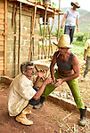 Cuban tobacco farmers sharing a cigar during a break on a construction job.