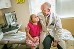 Aubrey Parks, 8, born with spina bifida, became the first patient at Duke to receive the MAGEC (MAGnetic Expansion Control) rod implant, recently approved by the FDA for treatment of early onset scoliosis. In about three years, Aubrey's MAGEC rods will reach their maximum length and pediatric spine surgeon, Robert Lark, MD, who has been treating Aubrey and recommended the MAGEC, will then perform a spinal fusion to connect together her vertebrae so that they no longer move. Here, Aubrey gives Dr. Lark a hug at Duke Orthopaedics of Raleigh. (Patient release on file at Duke Photography.)