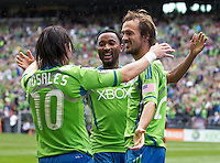 From left, Seattle Sounders FC midfielder Mauro Rosales, defender James Riley and forward Roger Levesque celebrate Levesque's goal during play against the Colorado Rapids at CenturyLink Field in Seattle Saturday July 16, 2011. The Sounders won the game 4-3.