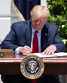 """United States President Donald J. Trump signs the presidential proclamation titled """"Maximizing Use of American-Made Goods, Products and Materials"""" as he hosts the Third Annual """"Made in America"""" Product Showcase on the South Lawn of the White House in Washington, DC on Monday, July 15, 2019.<br /> Credit: Ron Sachs / CNP"""