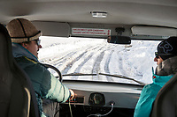 A frozen, rutted, snowy road as seen through the window of a car while traveling in Kyrgyzstan