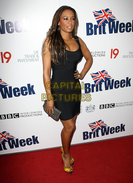 MEL B - MELANIE BROWN - SCARY SPICE.The BritWeek 2010 Champagne Launch held At The British General Consul Residence, Los Angeles, California, USA..April 20th, 2010.full length dress hand on hip clutch bag yellow gold peep toe silk satin shoes black cleavage .CAP/ADM/KB.©Kevan Brooks/AdMedia/Capital Pictures.