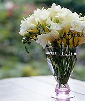 Cut freesia in a pink glass vase in the garden