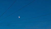 Moon in the early night sky framed by telephone cables.