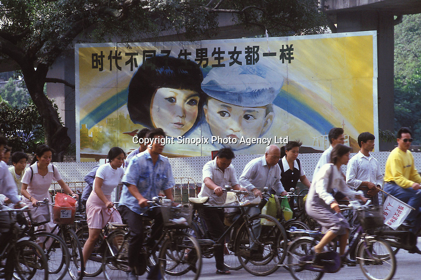 "Comuters pass a Government Propaganda poster that says ""boys and girls are equal in society"". An average gender inbalance of 118 males to 100 females caused by the strict One Child Policy and the preference for boys means that there is a shortage of women in China."