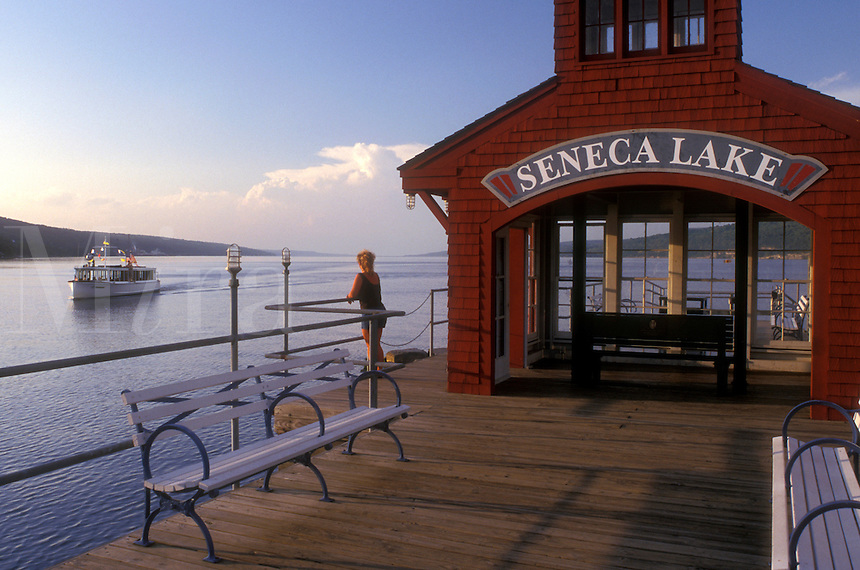 New York, Finger Lakes, Woman watches Captain Bill's Seneca Lake Cruise, the Stroller IV, sightseeing boat from the Watkin's Glen Public Pier on Seneca Lake in Watkins Glen