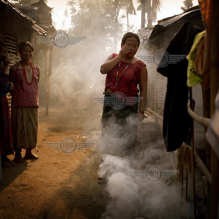 A woman at a Bhutanese refugee settlement standing amidst smoke from a fire...